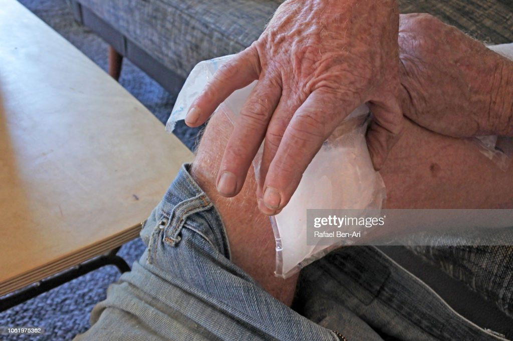 Man Placing an Ice Pack on his Wounded Leg after Home Accident : Stock Photo
