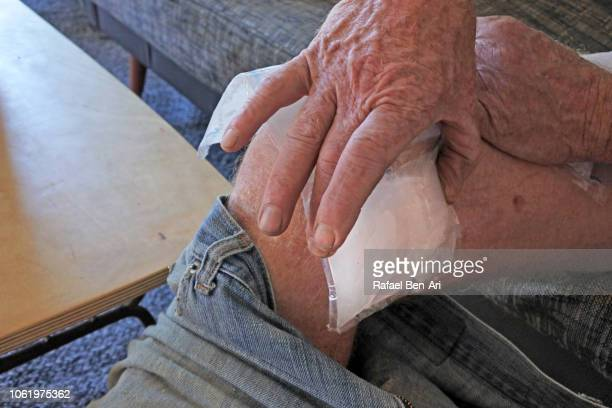 Man Placing an Ice Pack on his Wounded Leg after Home Accident