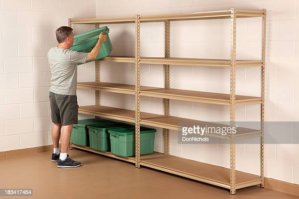man placing bin on shelf - storage compartment stock pictures, royalty-free photos & images