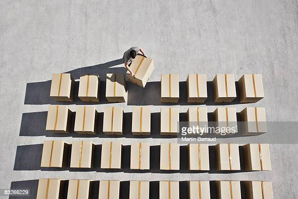 man placing box into line - repetition stock pictures, royalty-free photos & images