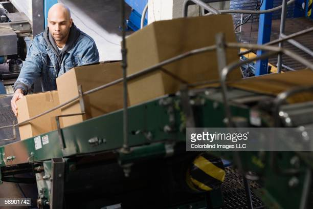 Man placing boxes on conveyor belt