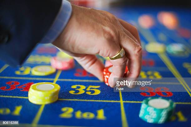 Man Placing Chips on Roulette Table