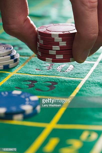 A man placing gambling chips on number 30, detail of fingers