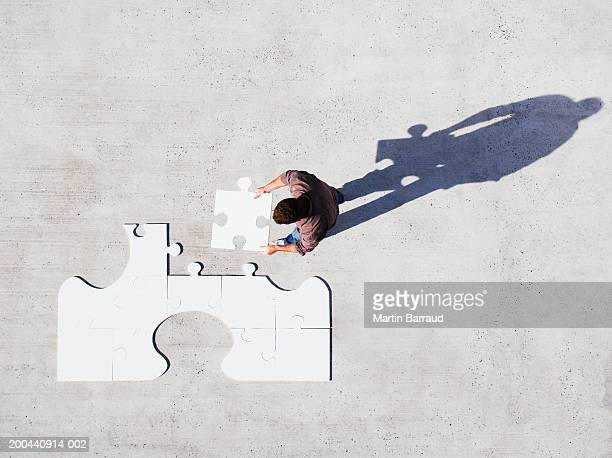 Man placing jigsaw piece into jigsaw, overhead view