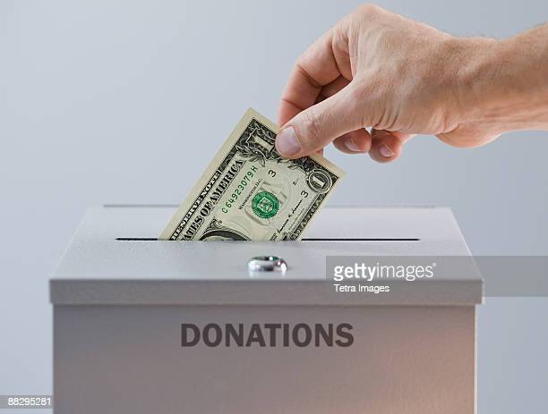 Man placing money in donation box