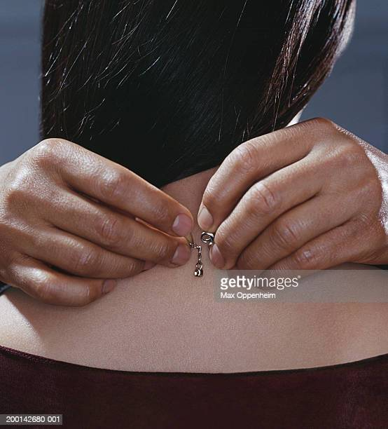 man placing necklace on woman, close-up - necklace stock pictures, royalty-free photos & images