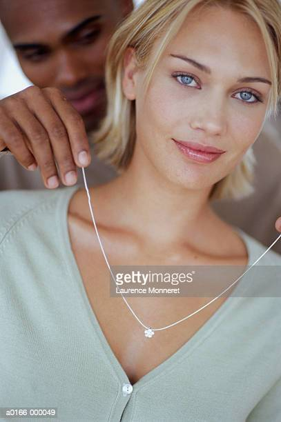 Man Placing Necklace on Woman