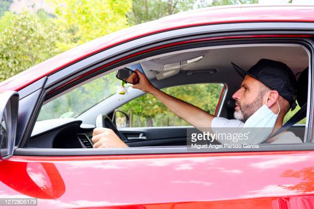 man placing the mirror with face mask - stock photo. - travelstock44 stock pictures, royalty-free photos & images