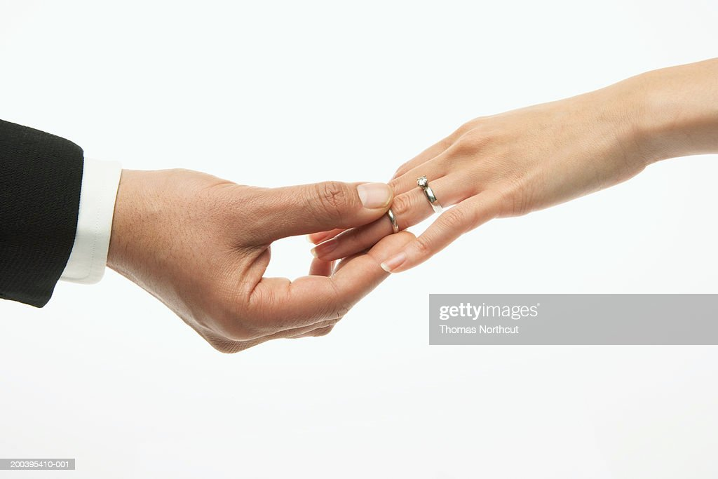 Man placing wedding band on woman's hand (focus on hands) : Stock Photo