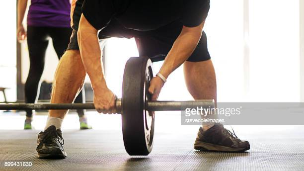 Man placing weight onto free weight barbell.