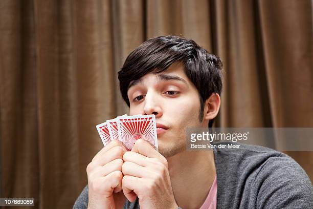 man plaing poker, looking at cards. - poker card game stock photos and pictures