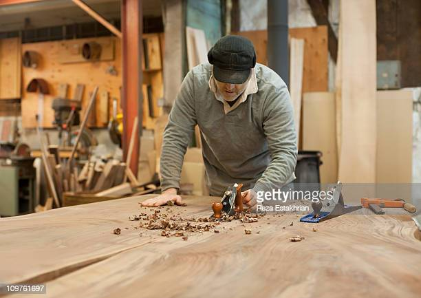 Man planes wood for table top
