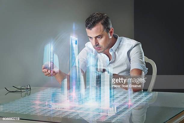 Man planning contruction work over table hologram