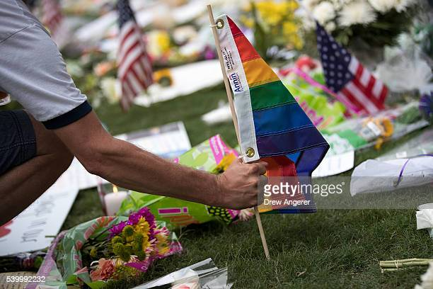 A man plants a Pride flag at a makeshift memorial prior to an evening vigil for the victims of the Pulse Nightclub shootings at the Dr Phillips...