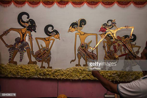 A man play a shadow puppets in Wukirsari Imogiri Bantul Yogyakarta Indonesia on May 23 2016 Shadow puppets are made of buffalo skin an Indonesian...