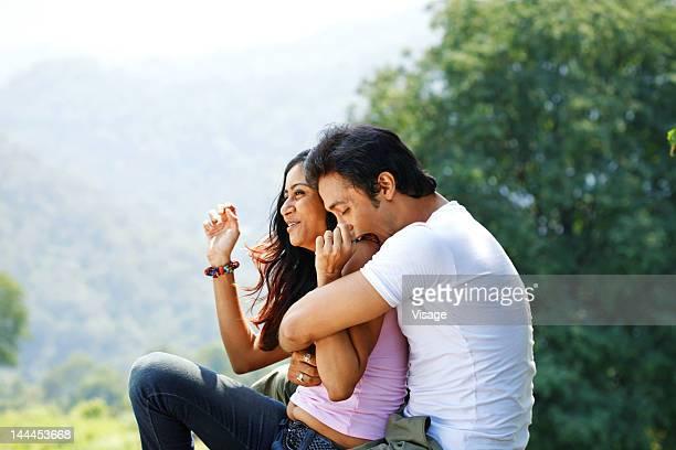 Man playfully biting his girlfriend