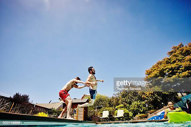Man playfully pushing friend into pool
