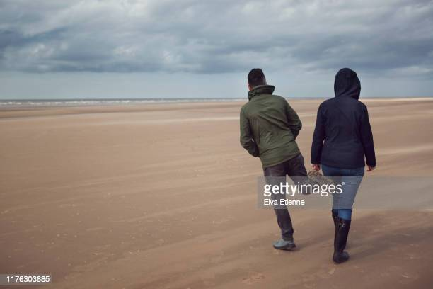 man playfully tapping woman with his foot whilst walking along a beach in england on a cold and windy day - couple relationship stock pictures, royalty-free photos & images