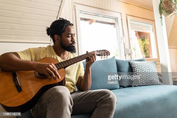 man playing a guitar at home. - african american culture stock pictures, royalty-free photos & images