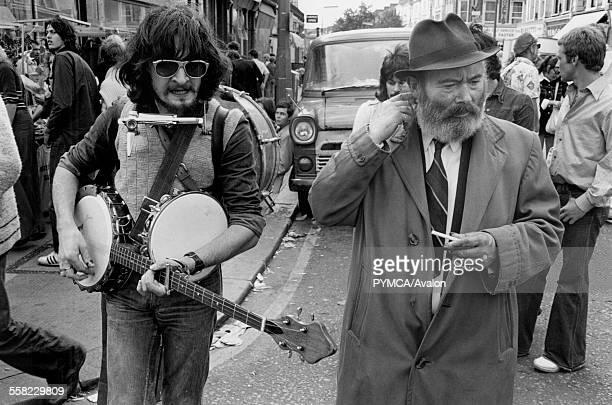 Man playing a guitar at Portobello Road market London August 1975