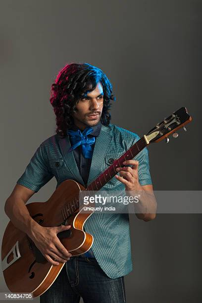 man playing a guitar - modern rock stock pictures, royalty-free photos & images