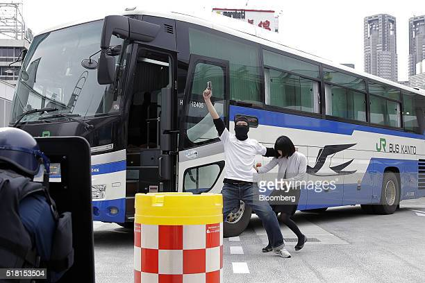 A man playing a role as a bus hijacker holds up a mock pistol next to a woman playing a role as a hostage while members of the Emergency Response...