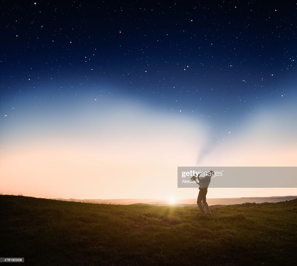 Man playing a saxophone at sunset : Stock Photo