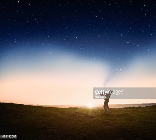 Man playing a saxophone at sunset