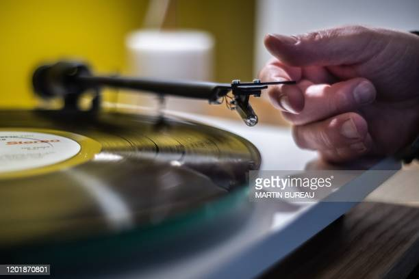 Man playing a turntable vinyl record player in a music store in Paris, on February 18, 2020.