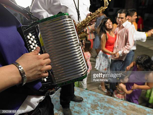 Man playing accordion, people dancing in background