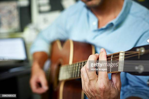 man playing acoustic guitar at home - acoustic guitar stock pictures, royalty-free photos & images