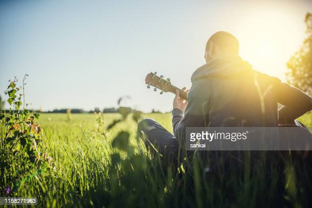 man playing acoustic guitar outdoors - country and western music stock pictures, royalty-free photos & images