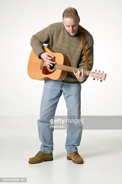 Man Playing Acoustic Guitar Posing In Studio Portrait