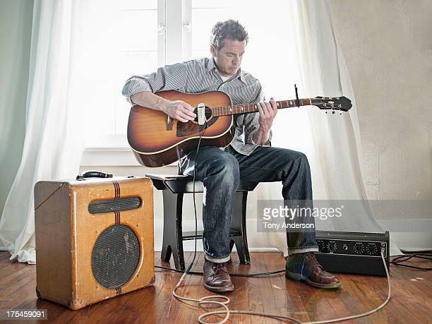 man playing acoustic guitar with electric pick up - one mature man only stock pictures, royalty-free photos & images