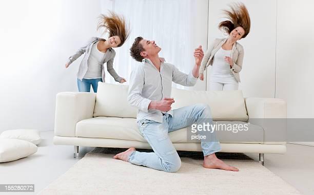Mann spielt Luftgitarre spielen und zwei tanzenden jungen Frauen
