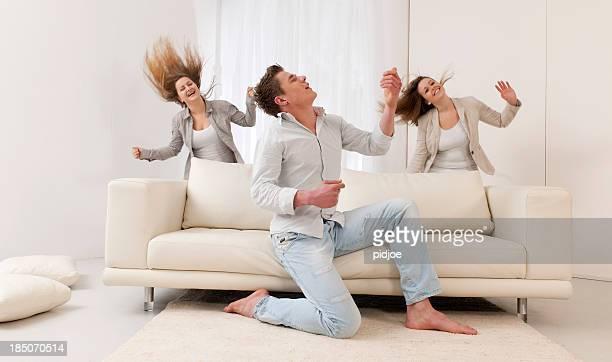 Hombre tocando la guitarra de aire y dos mujeres jóvenes bailando