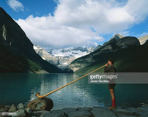 Man Playing Alpenhorn by Lake Louise