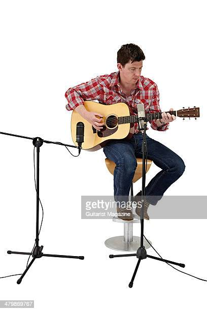 This image has been digitally manipulated) A man playing an acoustic guitar in a recording situation using a pair of condenser microphones,...