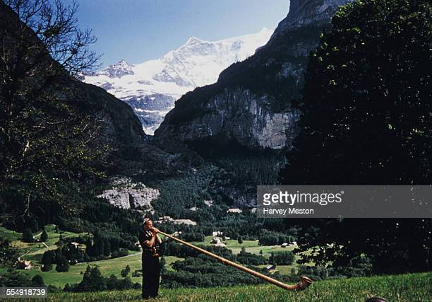 A man playing an alphorn or alpine horn in Grindelwald Switzerland circa 1965