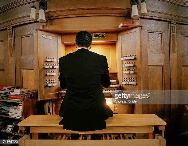 a man playing an organ in a church. - church organ stock pictures, royalty-free photos & images