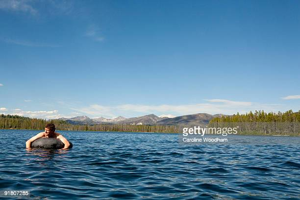 Man playing at a mountain lake in summer.