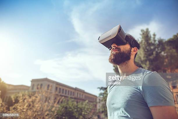 man playing augmented reality with vr headset - realtà aumentata foto e immagini stock