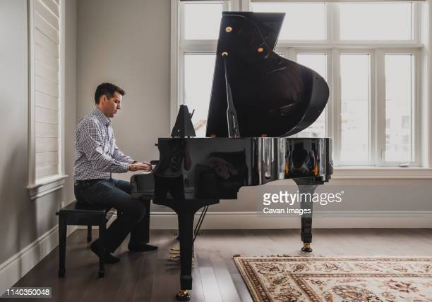 man playing baby grand piano in a bright room - grand piano stock pictures, royalty-free photos & images