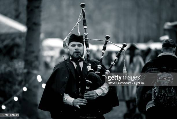 Man Playing Bagpipe While Standing Outdoors