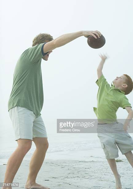 Man playing ball with son on beach