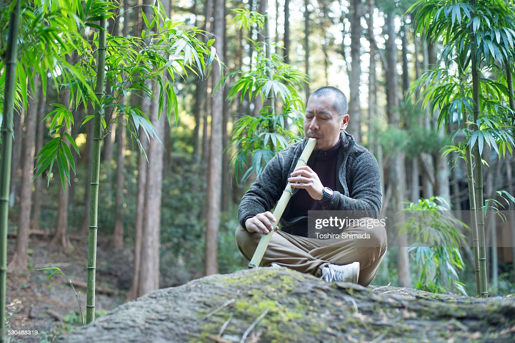 A man playing bamboo flute in the bamboo forest : Stock Photo
