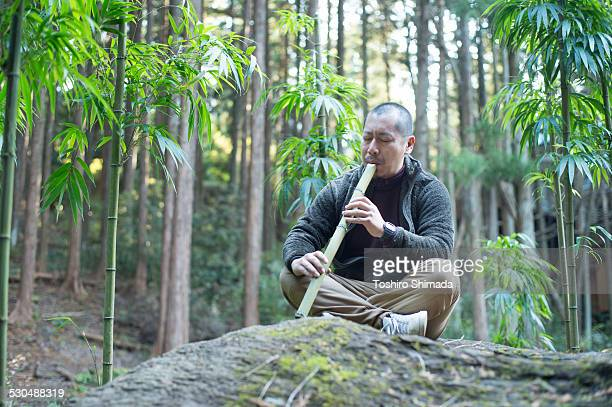 a man playing bamboo flute in the bamboo forest - bamboo flute stock photos and pictures