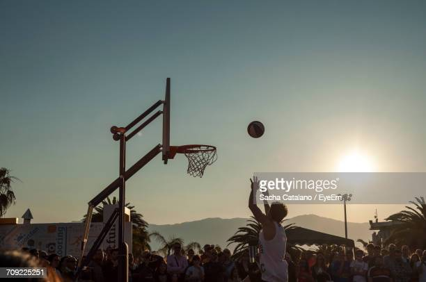 Man Playing Basketball In Front Of Crowd During Sunset
