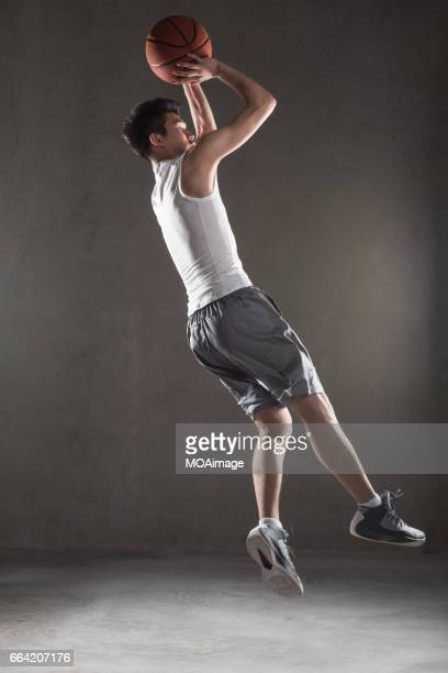 man playing basketball on gray background - taking a shot sport stock pictures, royalty-free photos & images