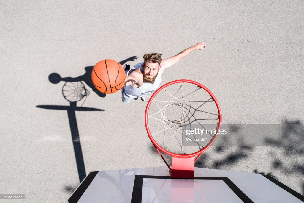 Man playing basketball on outdoor court : Stock Photo